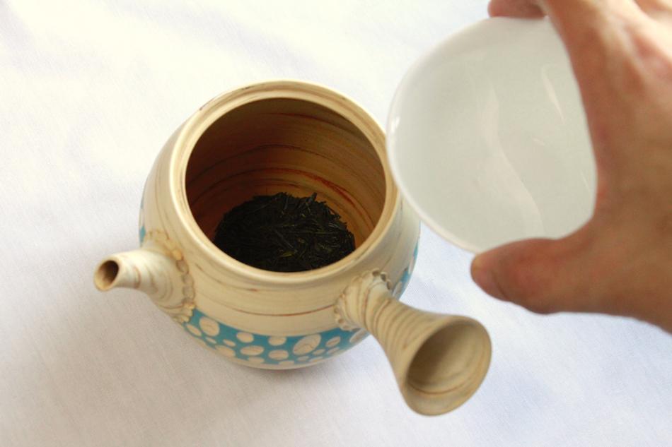 お茶の入った急須にお湯を注ぐ